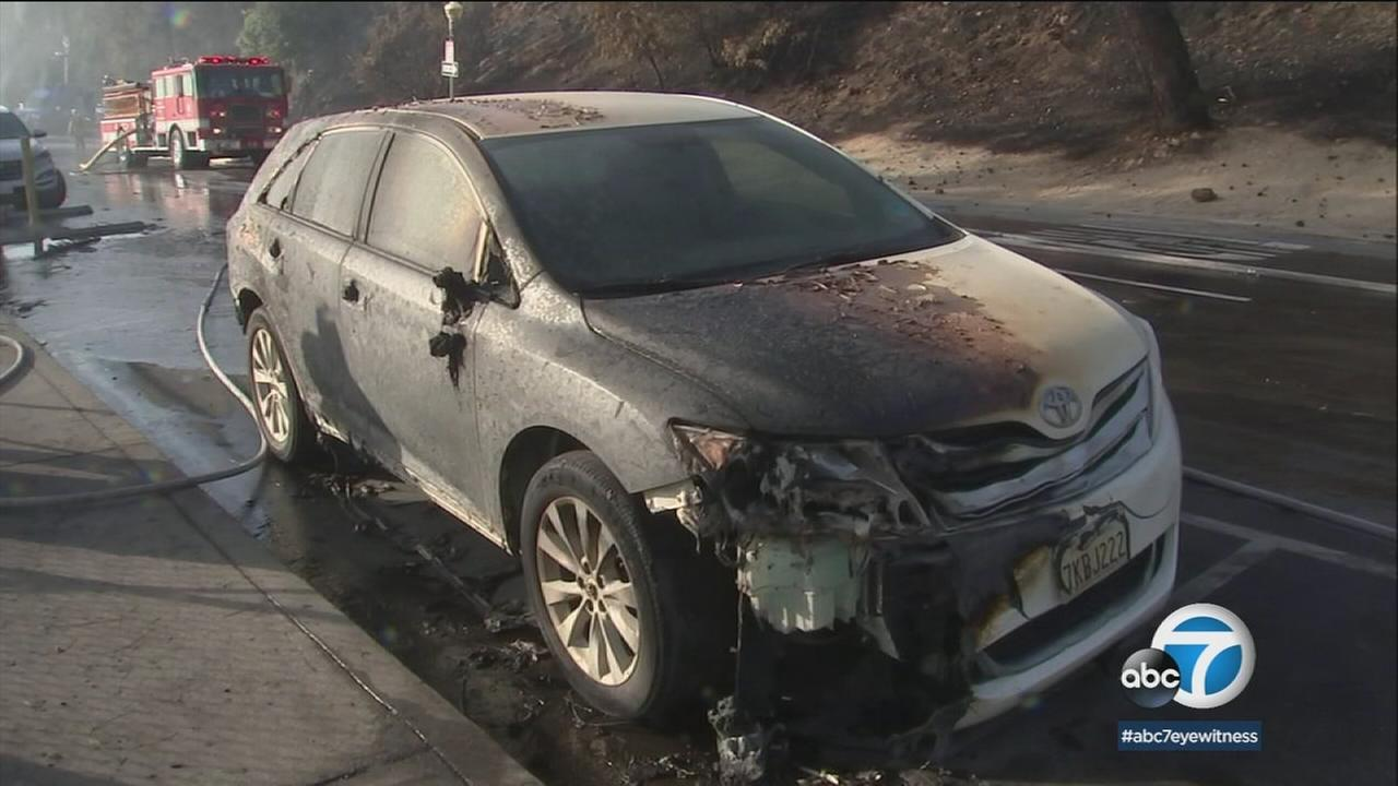 A vehicle damaged by a small brush fire that erupted in Griffith Park is shown in a photo.
