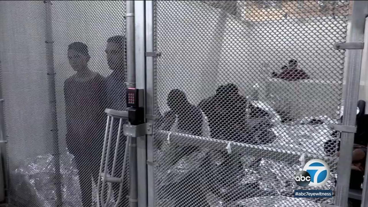 People in cages are shown at a detention center.