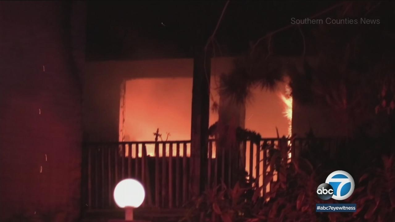 A suspicious fire that ripped through a Santa Ana apartment injured three people, one of whom was detained for questioning, authorities said.