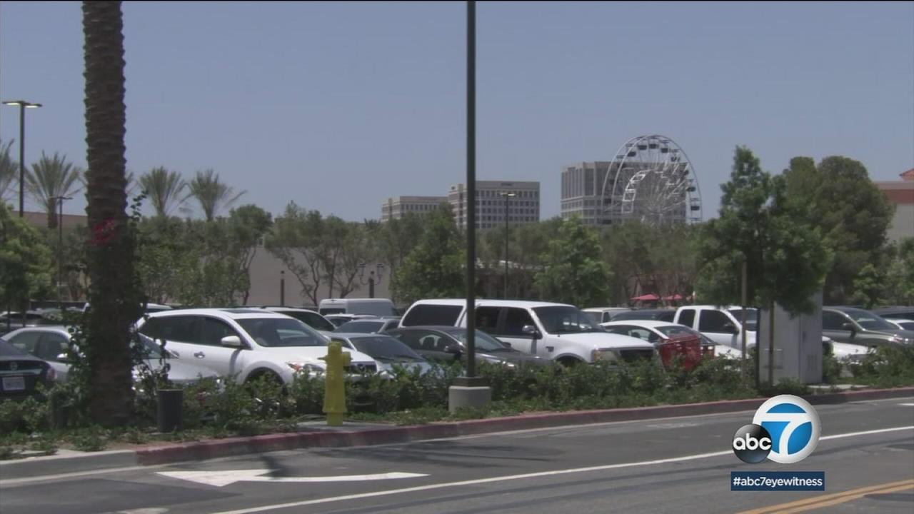 Vehicles are shown at a parking lot in a shopping center in Orange County.