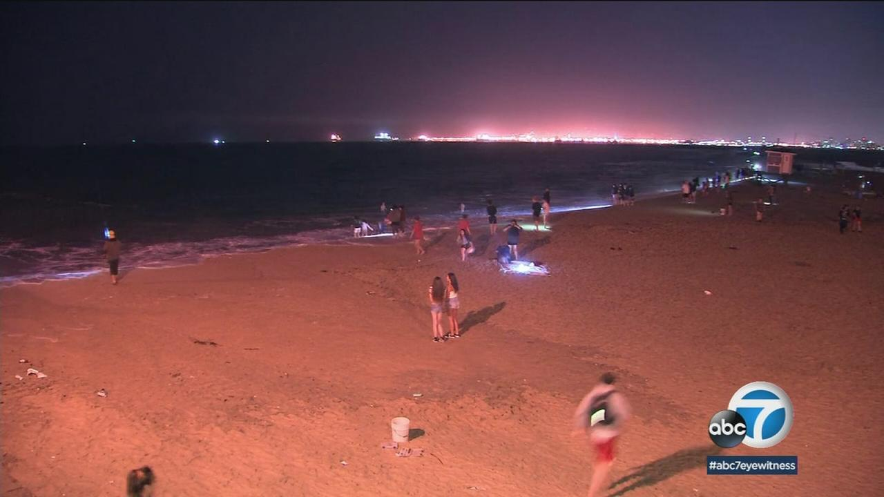 Beachgoers checked out the high tide in Seal Beach at night on a warm Saturday.