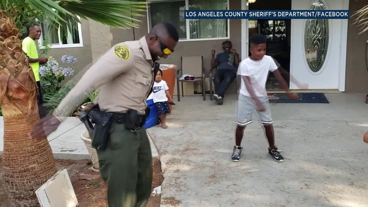 Deputy Vic Ekanem dances with a young boy at a home in Palmdale after responding to an accidental 911 call.