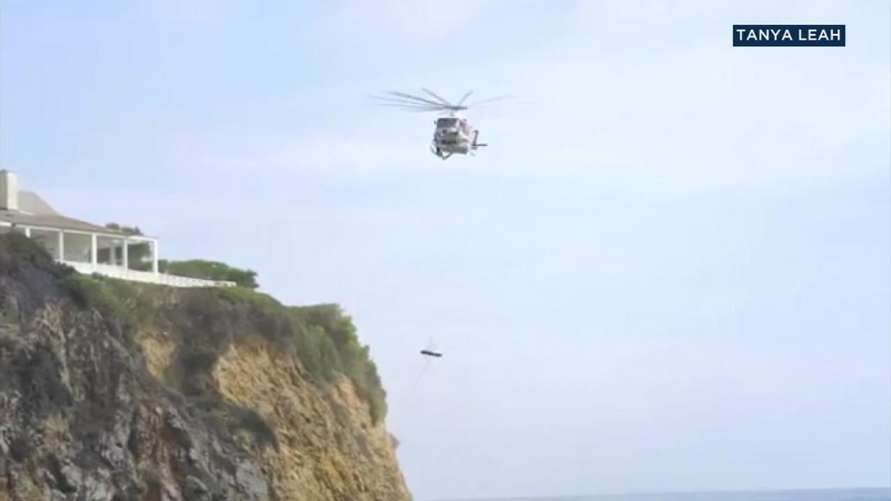Authorities airlifted a teenager from a steep cliff in Laguna Beach after a rock severed his arm and crushed his leg.
