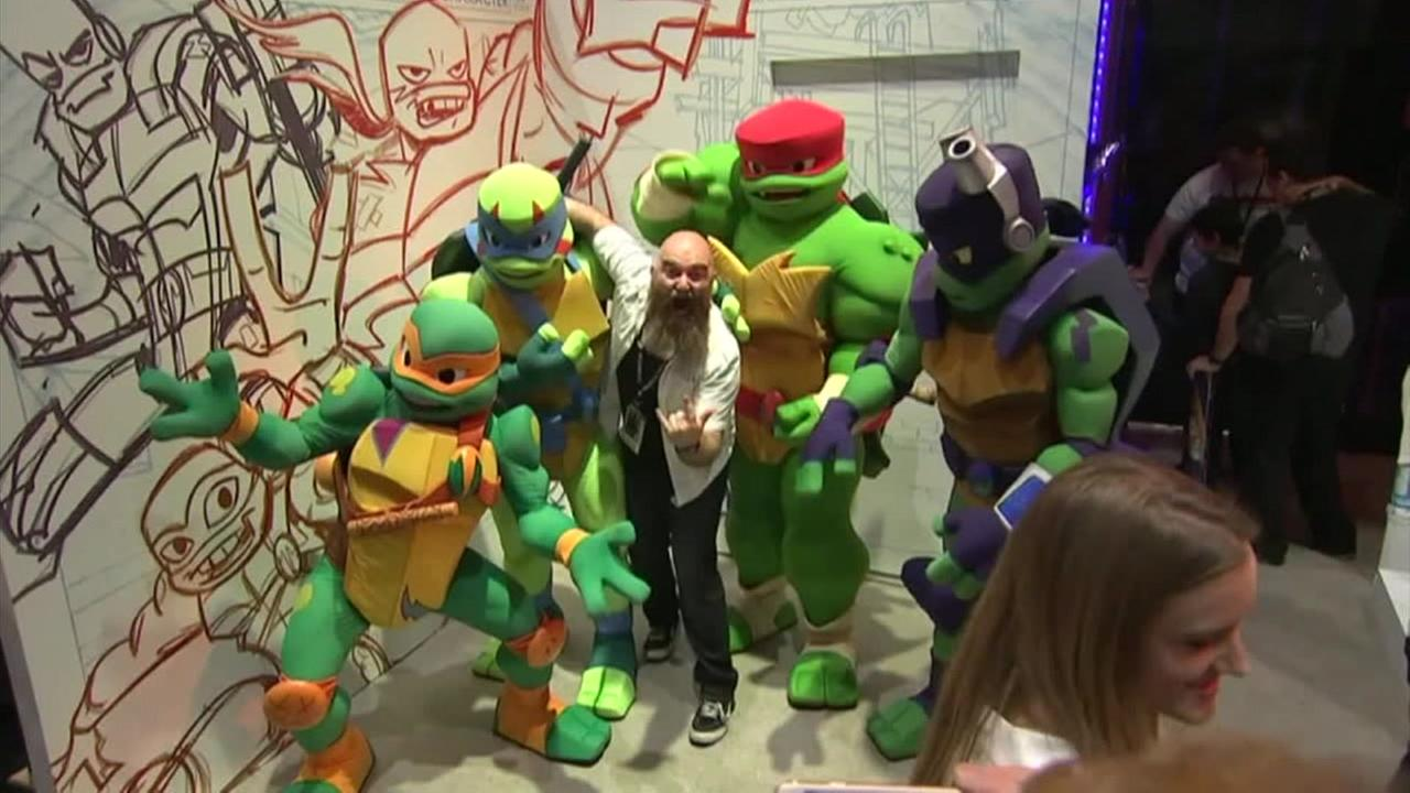A fan poses with Teenage Mutant Ninja Turtles in costumes at San Diego Comic-Con.