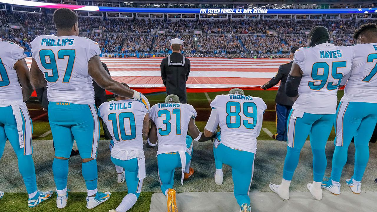 Miami Dolphins Jordan Phillips stands during the national anthem, but shows support for the protest as he puts an arm on the shoulder of kneeling teammate, Kenny Stills.