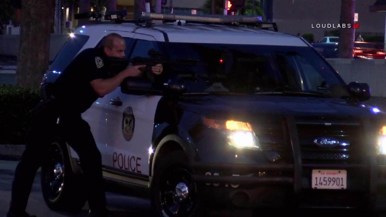A police officer aims a rifle at a driver after a high-speed chase ended in Riverside on Friday, July 21, 2018.