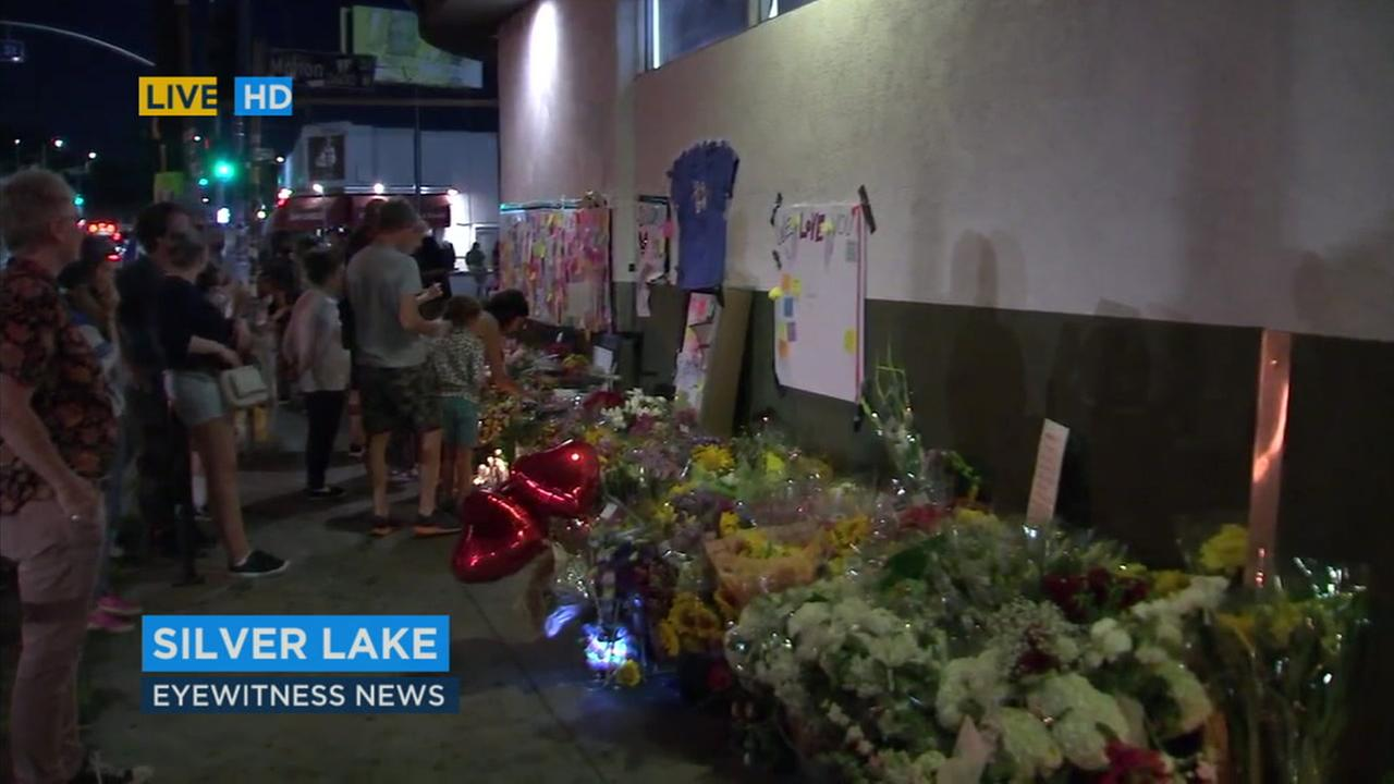 Memorials pay tribute to a manager at Trader Joes in Silver Lake who was killed when a suspect exchanged gunfire with police after a chase from South Los Angeles.