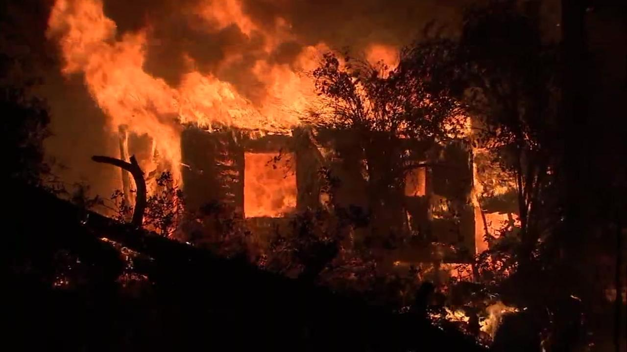 Flames tear through a home in Idyllwild after an intentionally set brush fire spread through the area Wednesday afternoon.