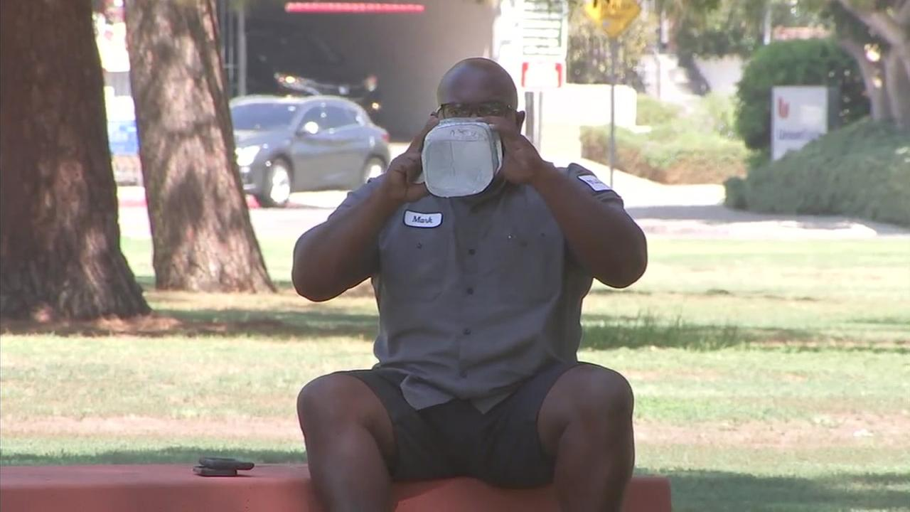 A man sits under the shade and drinks water as a way to combat the high heat in the San Fernando Valley.