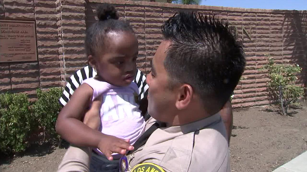 Baby Faith is taken into the arms of Deputy Castro, who saved her life last week.