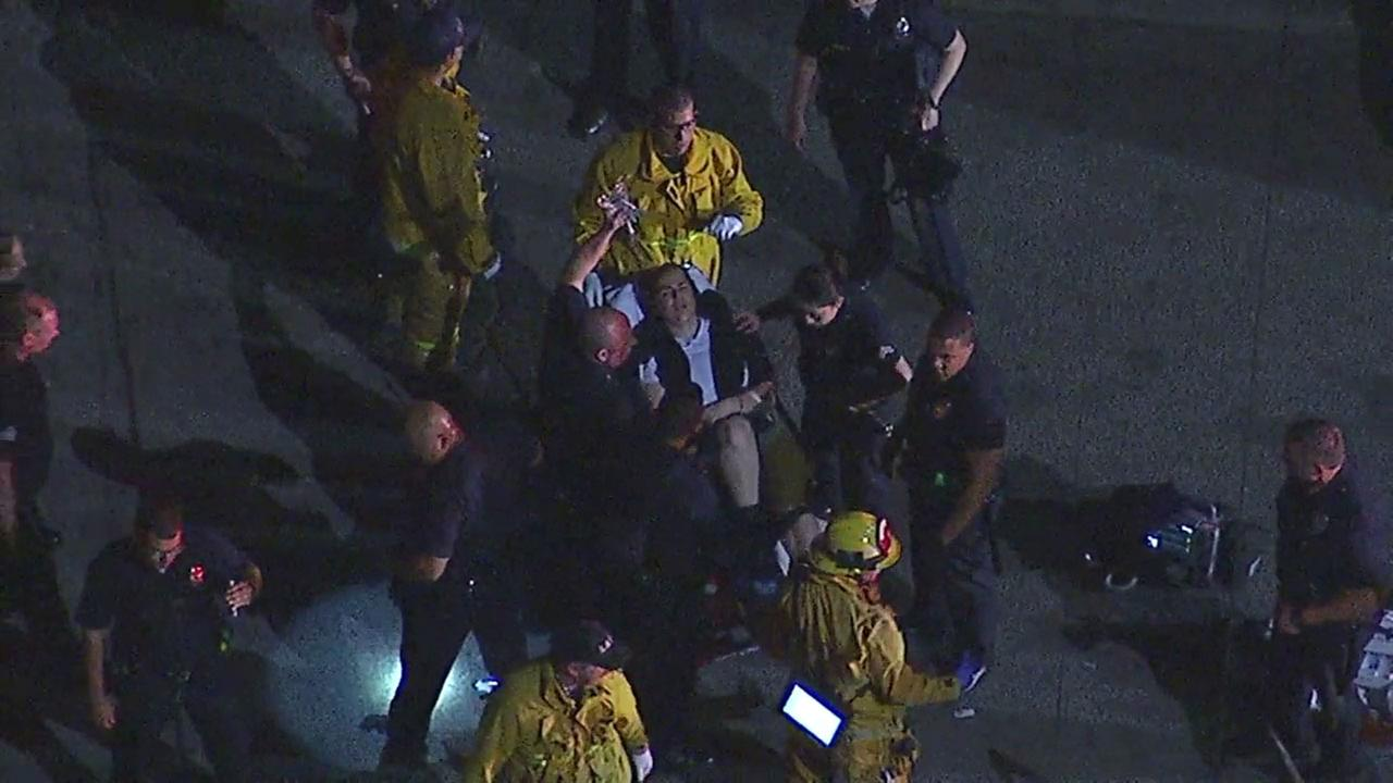 A female LAPD officer is loaded onto a gurney and wheeled to an ambulance after being shot in the leg during an officer-involved shooting in North Hills.