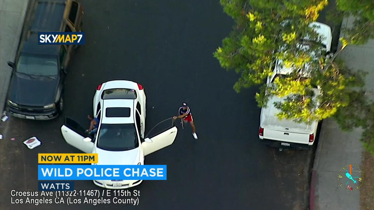 A robbery suspect is seen fleeing from a moving vehicle after a short chase that ended in Watts.
