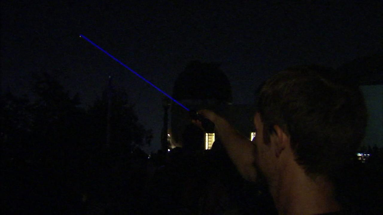 A person uses a blue laser to point at the location of Mars showing up in the sky above Griffith Observatory.
