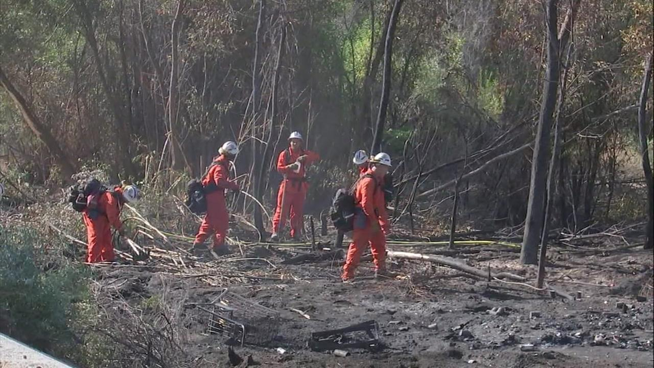 Fire crews mop up hot spots and clear debris in areas charred by the 10-acre Railroad Fire in Santa Clarita.