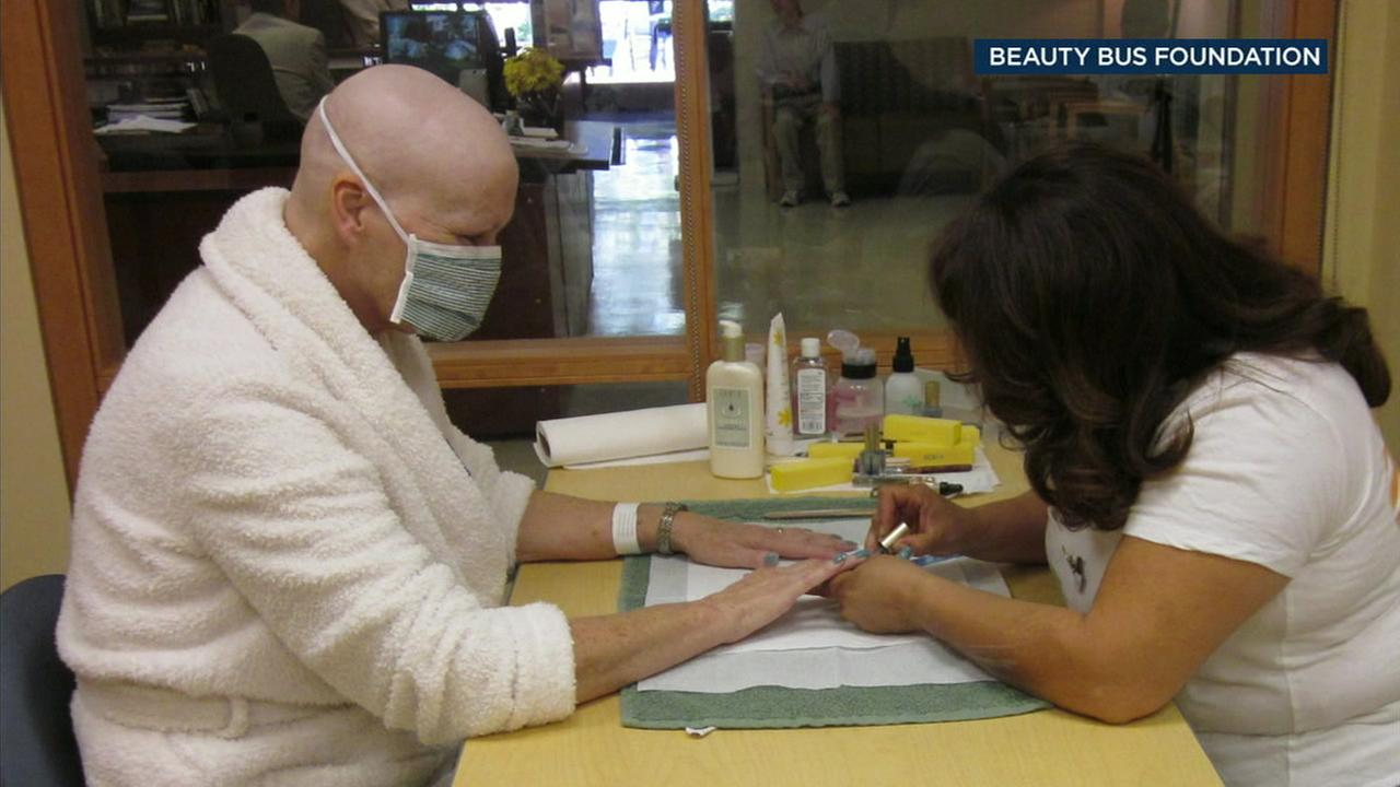 A patient has her nails done by a Beauty Bus volunteer.