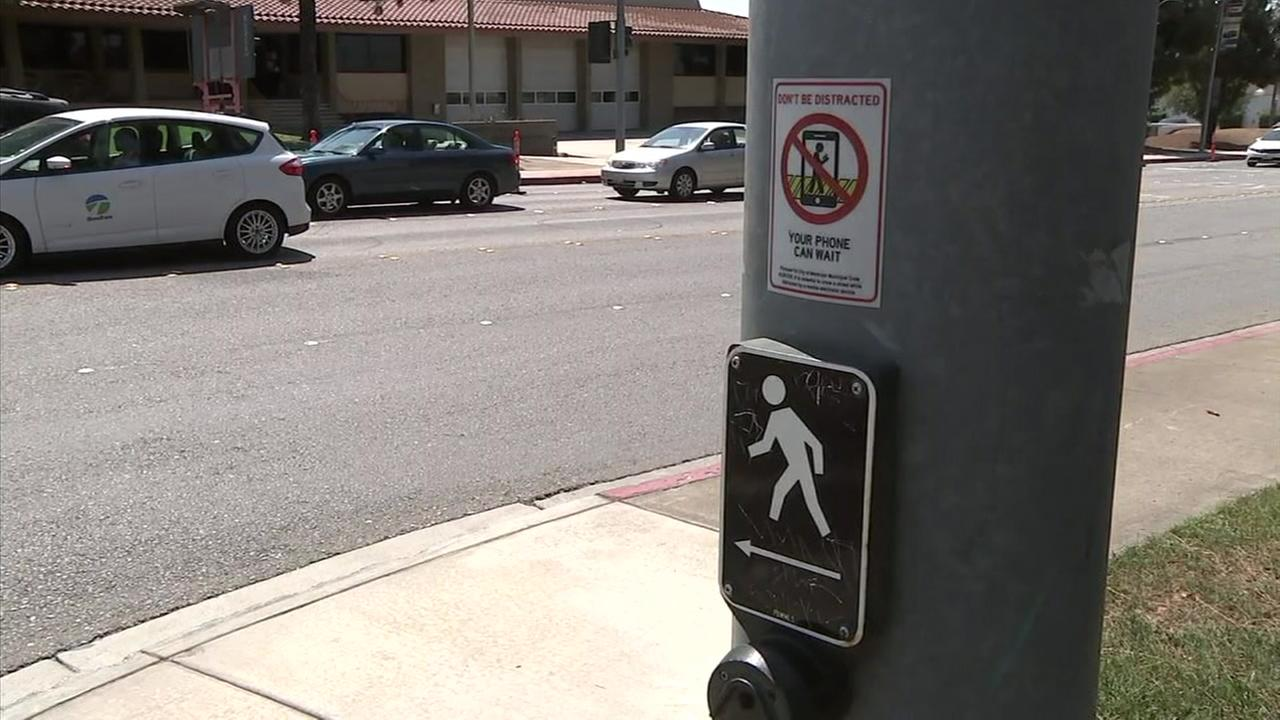 A sign shows no distractions, such as cellphones or headphones, should be used while crossing the street in Montclair.