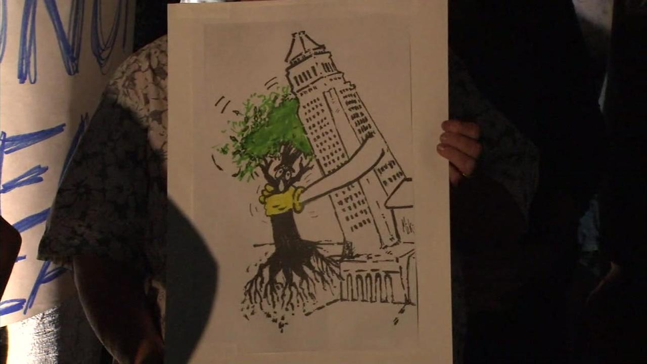 A protester holds up a sign that shows an anthropomorphic City Hall tearing out a tree.