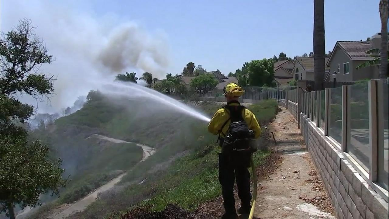 Firefighters and a resident used hoses to put out the flames and keep dry areas wet to keep from catching fire in Corona.