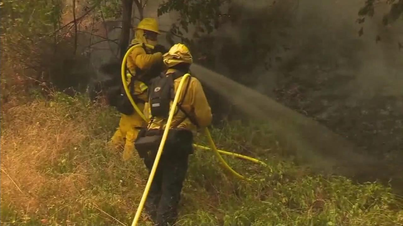 Firefighters try to put out flames and smoke amid hot Southern California temperatures.