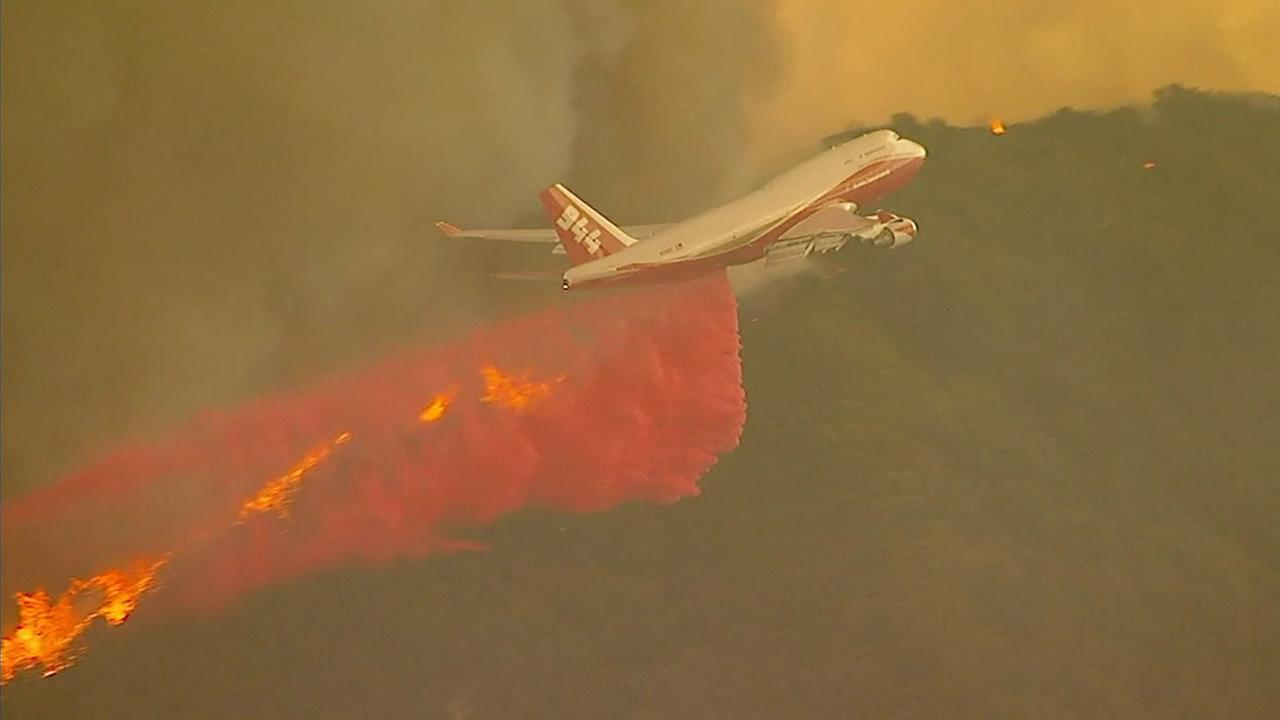 An airplane fire retardant drop is shown as firefighters battle a 4,000-acre brush fire in Orange Countys side of the Cleveland National Forest.