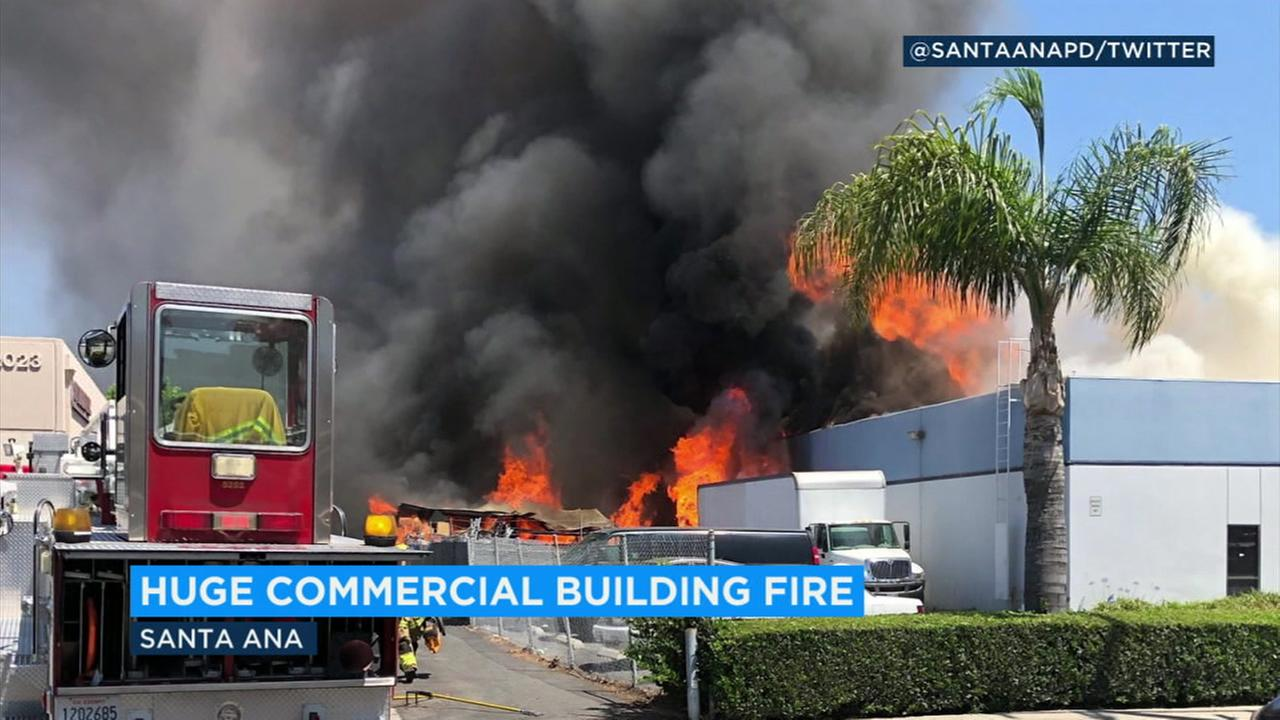 Firefighters responded to a fire in a commercial building in Santa Ana as flames and black smoke rose into the air.