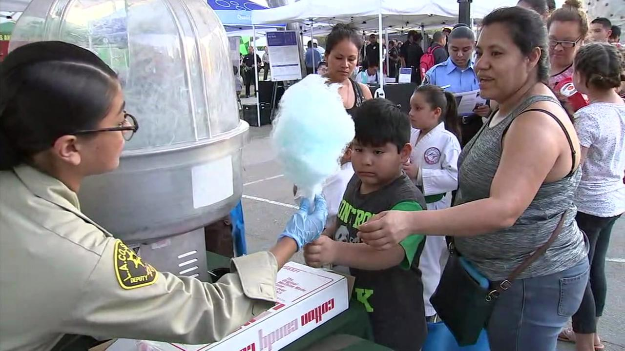 A Los Angeles County sheriffs deputy hands off some cotton candy to a local boy who participated in the National Night Out festivities.