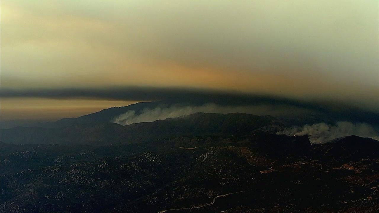 A giant cloud of smoke and ash hovers and obscures a mountainside in the Inland Empire near Orange County as the Holy Fire ravages the area.