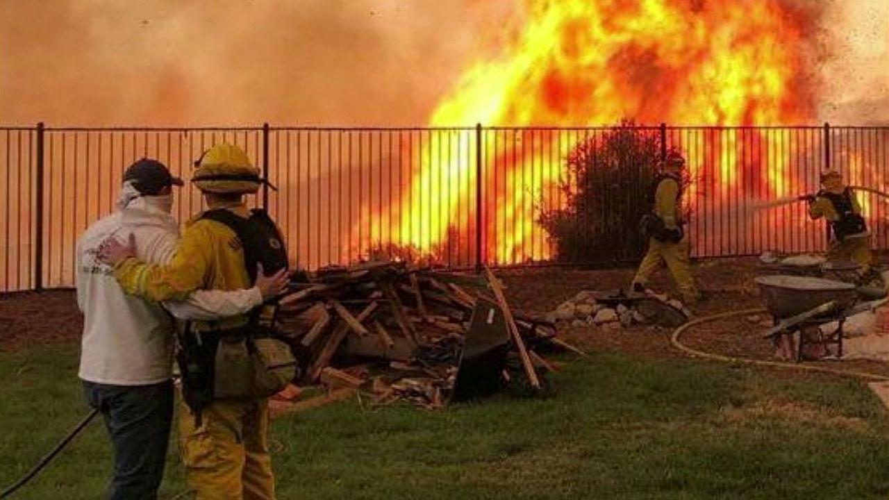 A Cal Fire firefighter hugs and consoles a man as he panics when Holy Fire flames get dangerously close to his sisters Lake Elsinore home.