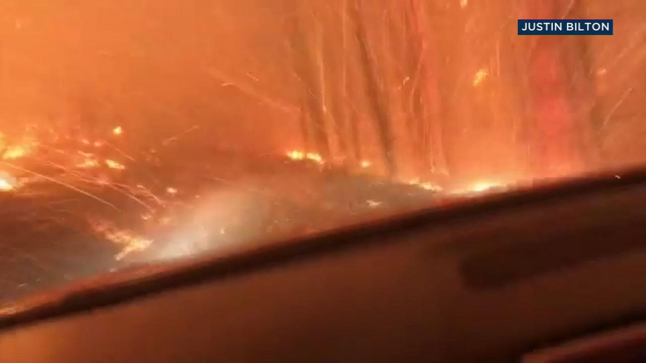 Flames ripped through trees and surrounded a car where a father and son were terrified as they drove through Glacier National Park.