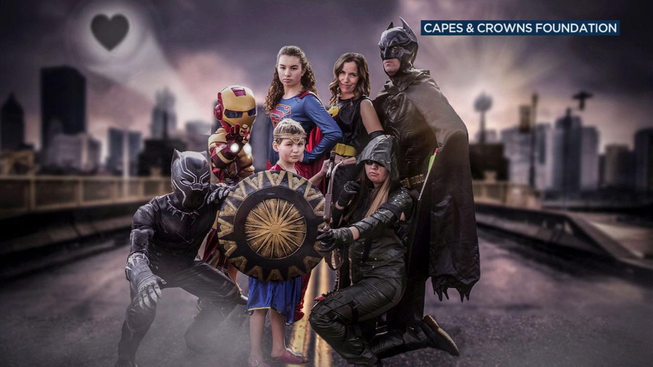 A family dressed as various superheroes from the Marvel and DC universes pose for a photo taken by nonprofit Capes and Crowns.