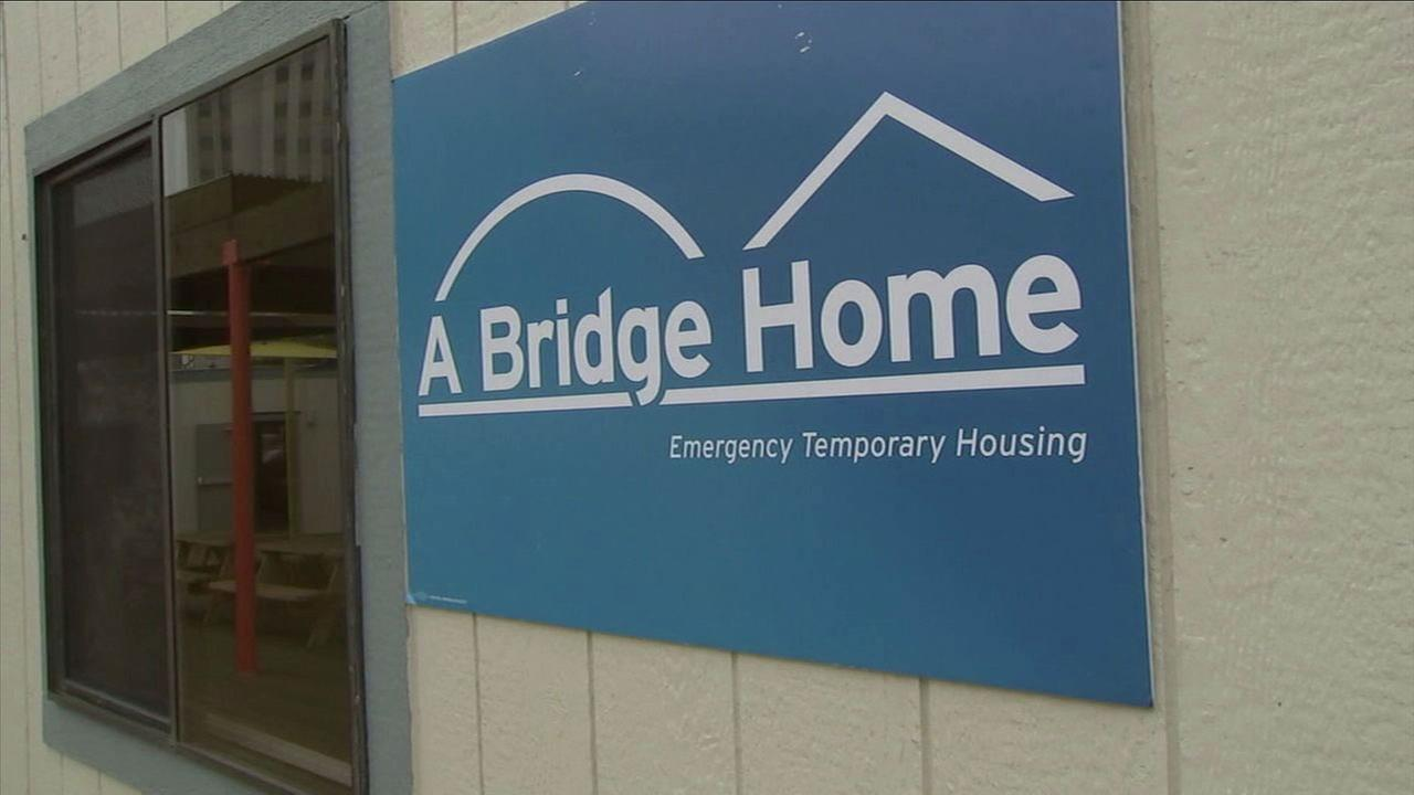 A sign for A Bridge Home, a new temporary homeless shelter in downtown Los Angeles, is shown in a photo.