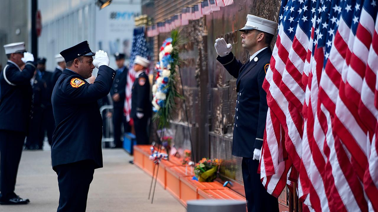 New York City firefighters salute in front of a memorial on the side of a firehouse adjacent to One World Trade Center and the 9/11 Memorial site during ceremonies.