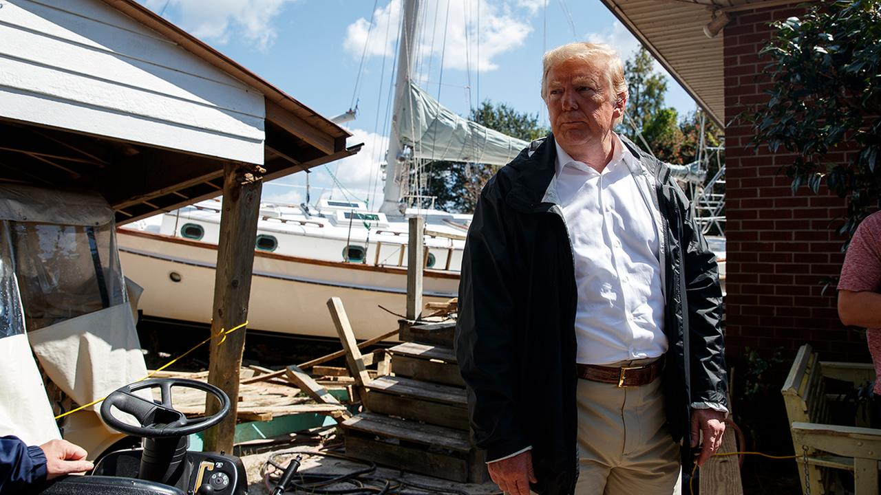 President Trump visits a house where a boat wash ashore in the backyard while touring a neighborhood impacted by Hurricane Florence, Wednesday, Sept. 19, 2018, in New Bern, N.C.