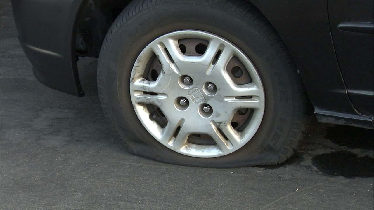 A deflated tire is seen in South Los Angeles after a vandal targeted nearly 100 vehicles overnight.