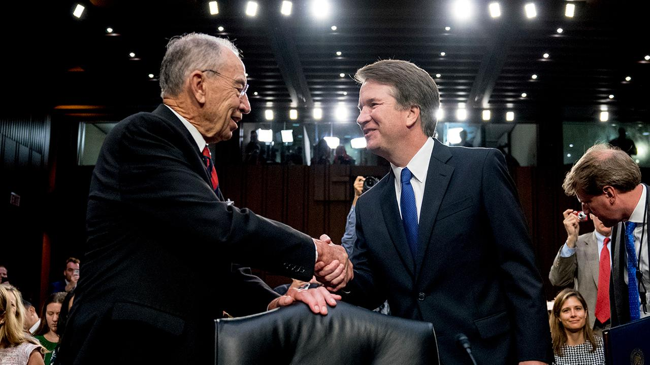 Supreme Court nominee Brett Kavanaugh, a federal appeals court judge, right, shakes hands with Senate Judiciary Chairman Chuck Grassley, R-Iowa.
