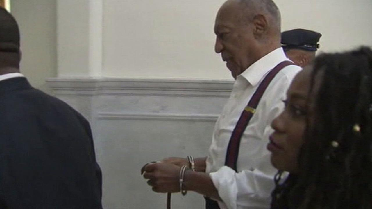 Bill Cosby is shown walking out of a Pennsylvania courtroom in handcuffs.