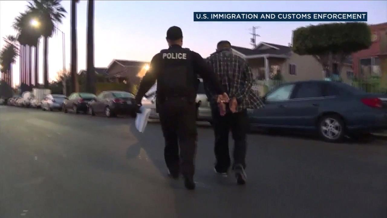 An ICE agent walks off with a person he arrested in a photo provided by the agency.