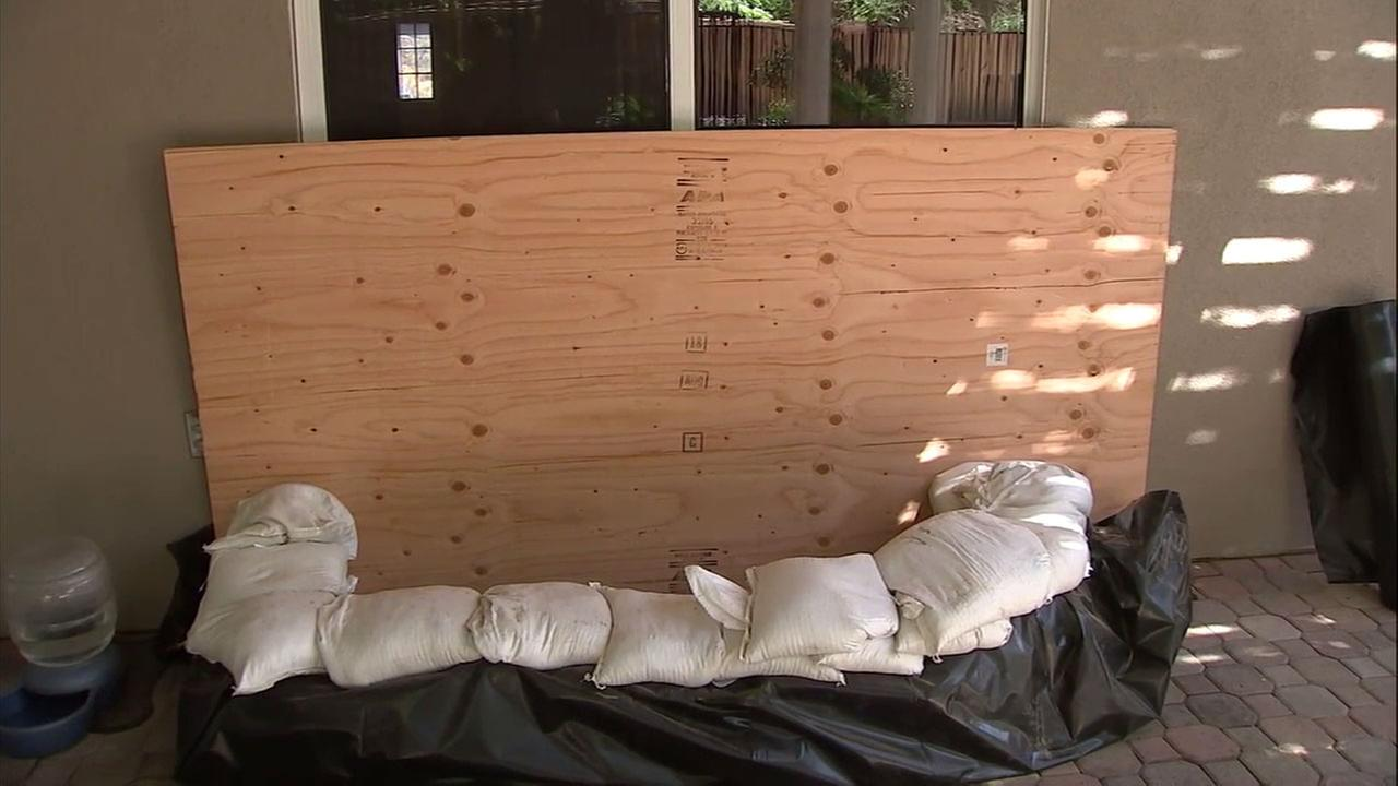 Sandbags and a large wood plank surround a sliding glass door at a Lake Elsinore home near the Holy Fire burn area in preparation for a rain storm.
