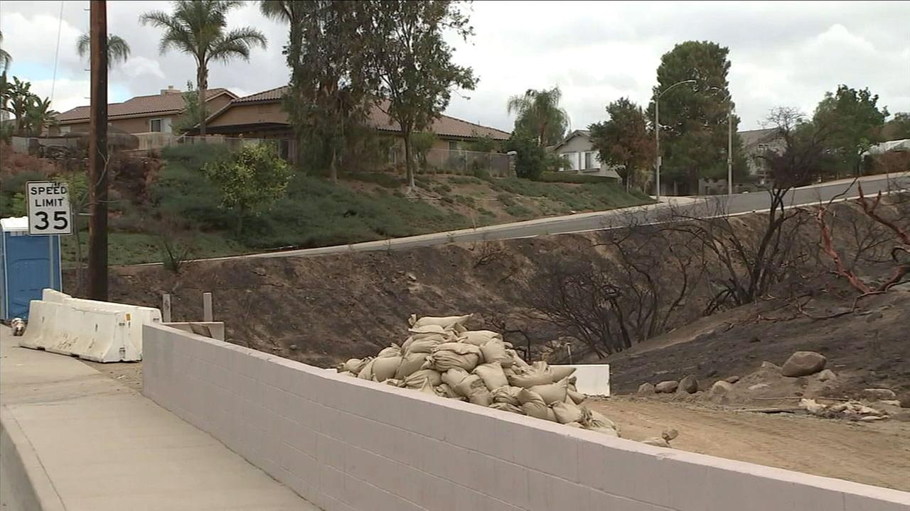 An burn area of Corona is being blocked off with K-rails and sandbags in preparation for a storm that is coming to the area.
