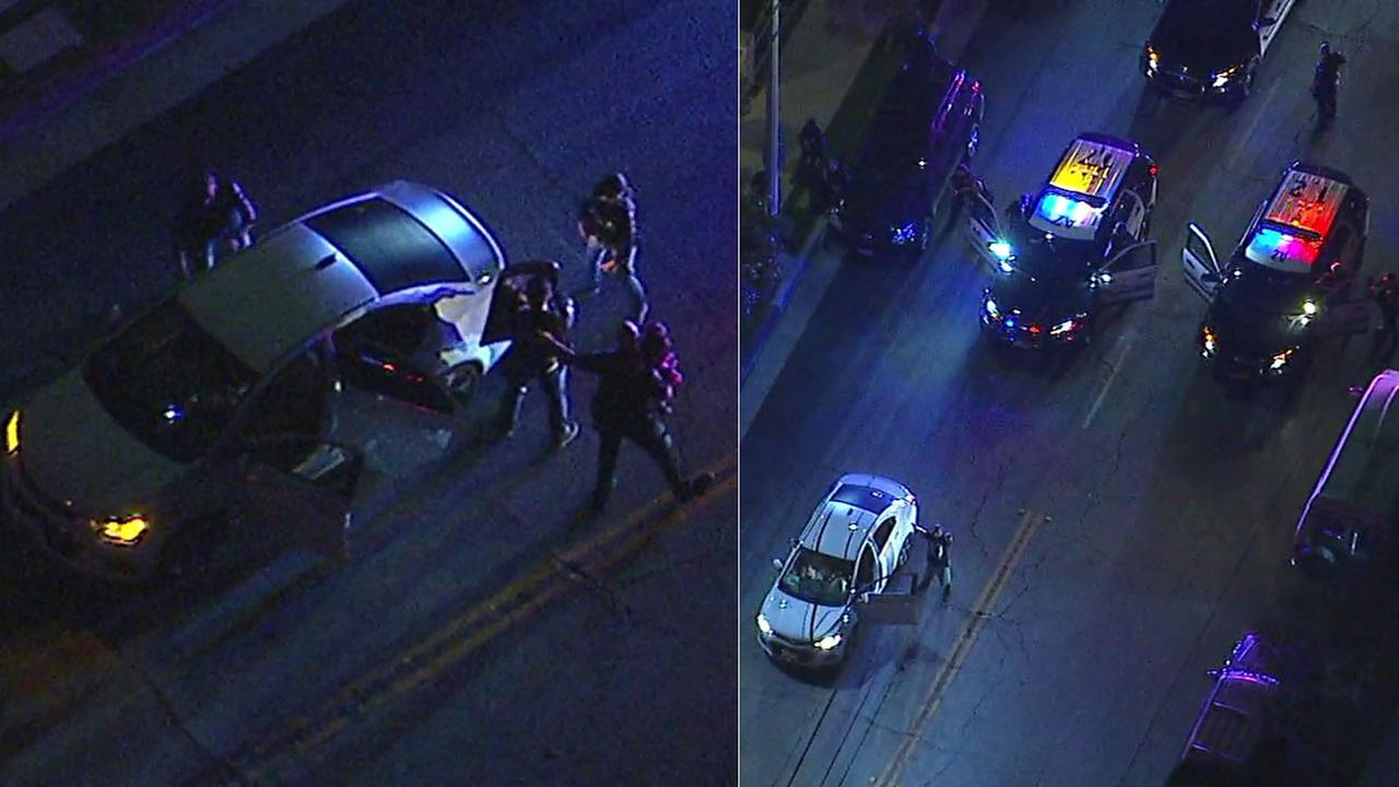 Authorities are shown taking out a small child from a vehicle as a suspect on the right is taken into custody following a chase in the San Gabriel Valley.