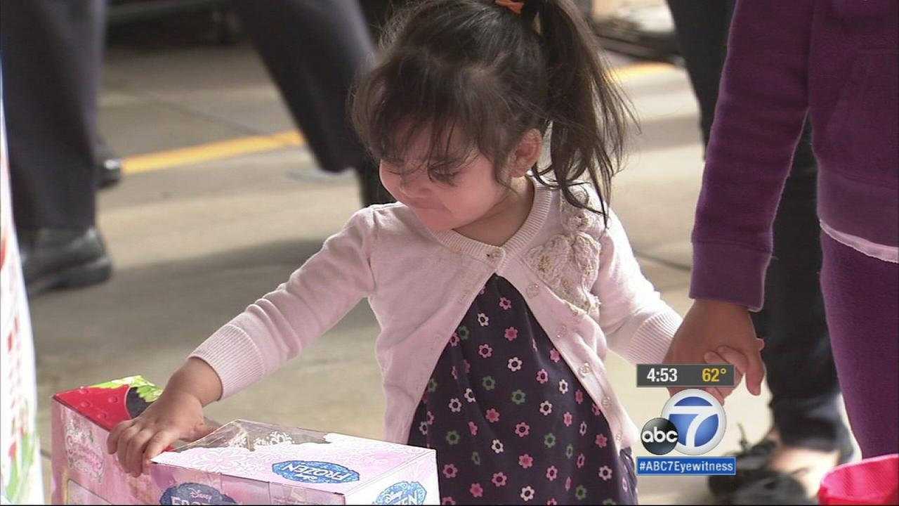 Blanca Rodriguezs daughter receives a toy from Spark of Love.