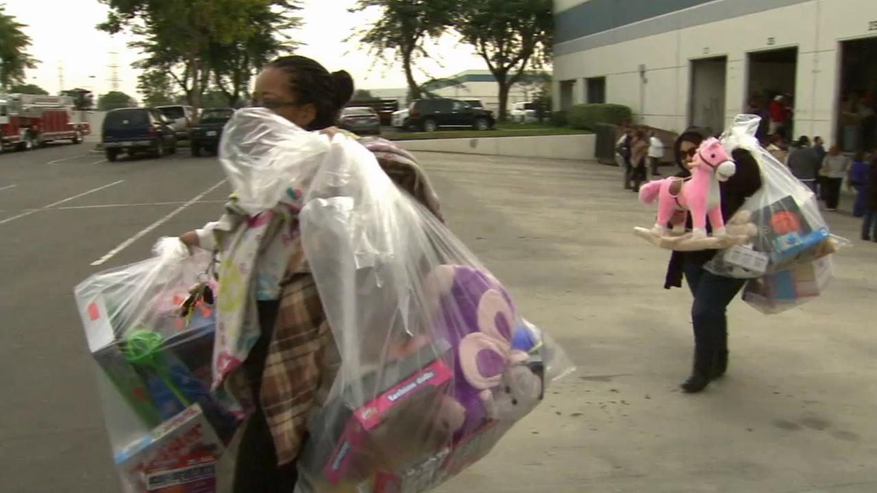 Two women walk away with toys donated to ABC7s Spark of Love toy drive on Saturday, Dec. 20, 2014.