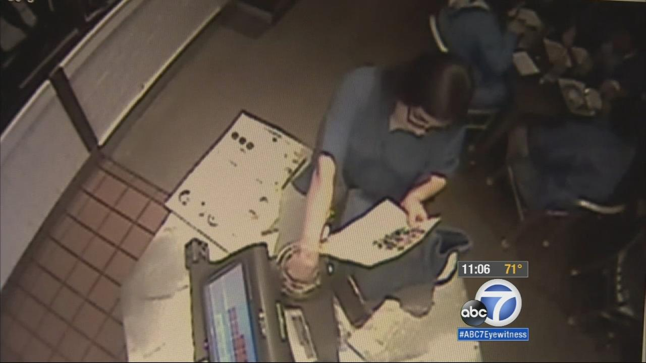 A woman was caught on camera stealing money from the tip jar.