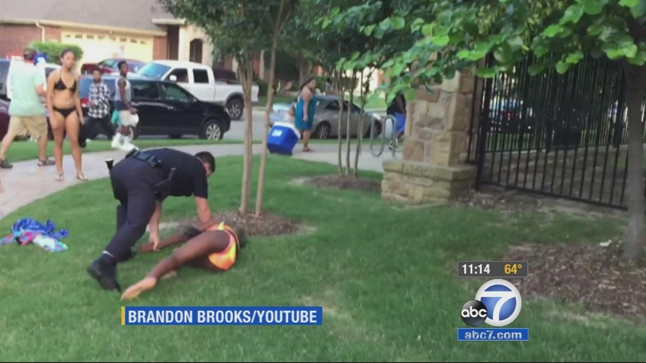 A suburban Dallas police officer has been placed on administrative leave after a video showed him pushing a 14-year-old girl in a swimsuit to the ground outside a pool and pointing his gun at other teens.