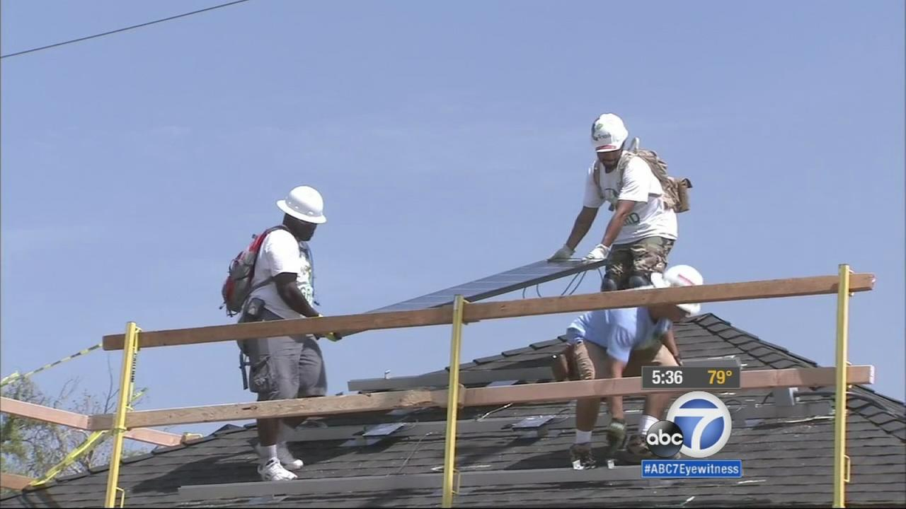 Volunteers with the nonprofit Grid Alternatives are installing solar panels as a way to help low-income families save money on renewable energy.