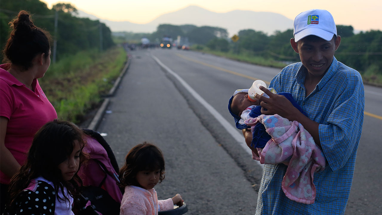 Guatemalan migrant Ernesto Cayax, 27, feeds his 25-day-old baby daughter Reychel, as he takes a break from walking with his wife Jahana Estrada, 23, and their three children.