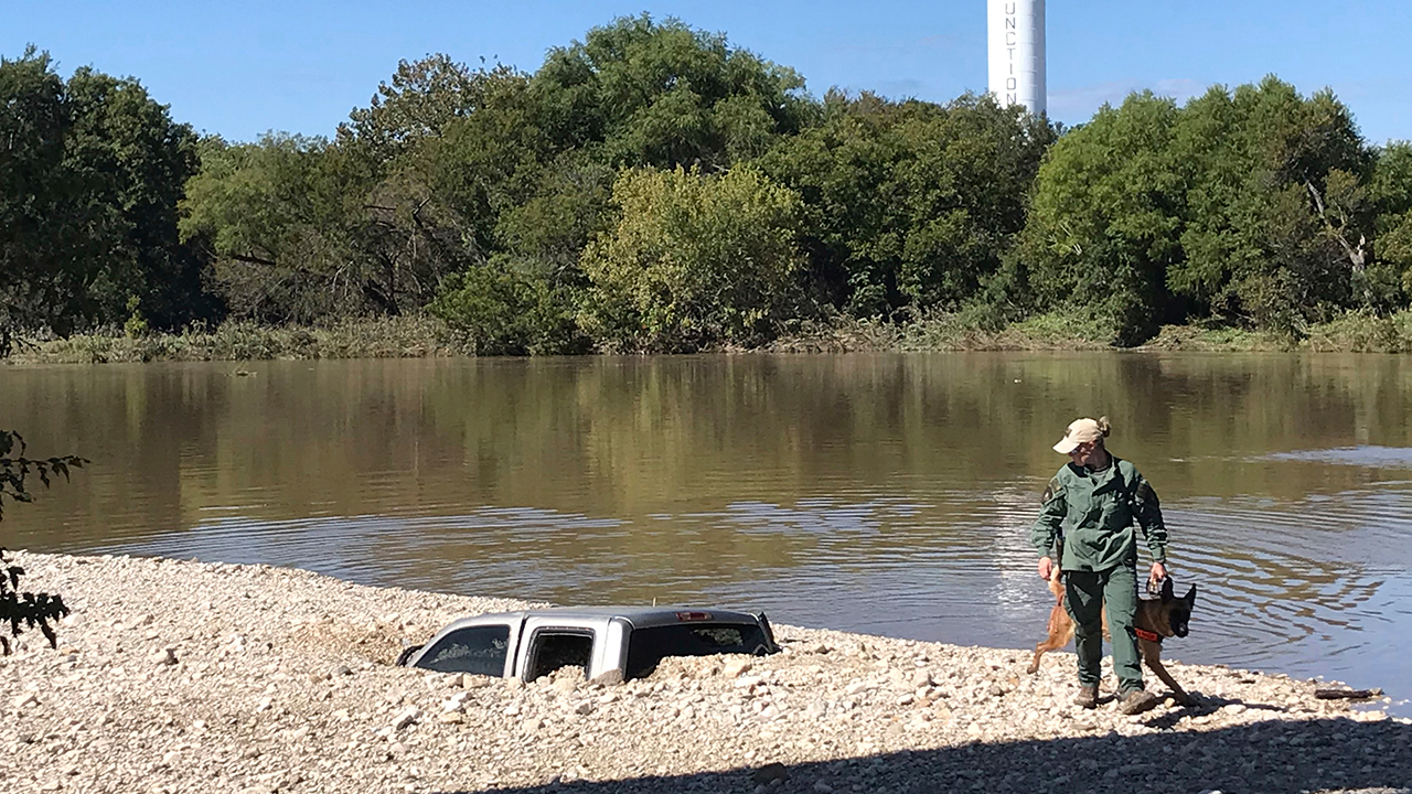 A member of the Texas Parks and Wildlife Game Warden K9 team walks past a buried truck as they continue the search Wednesday, Oct. 10, 2018, along the South Llano River.