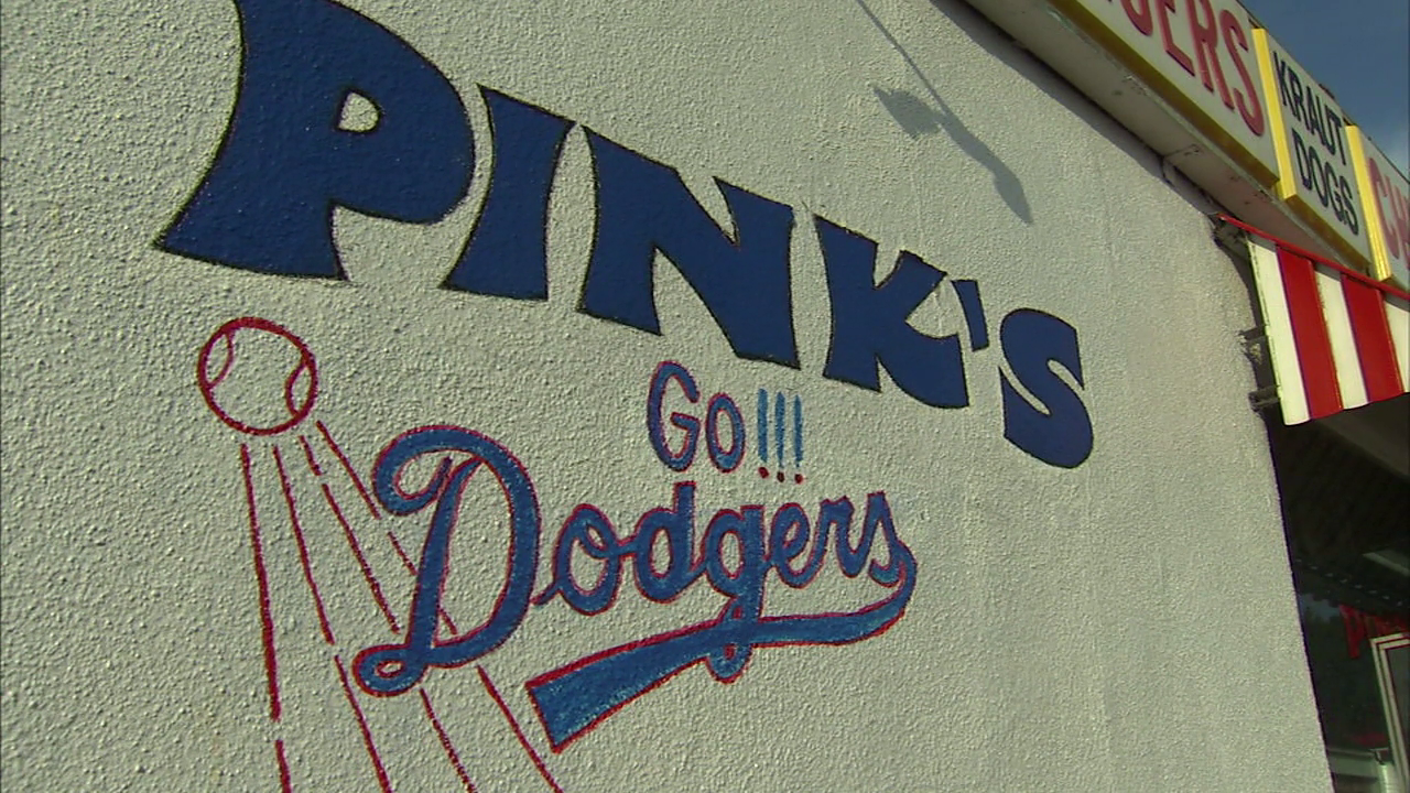 A handpainted logo saying Go Dodgers is on the side of the Pinks Hot Dogs building.