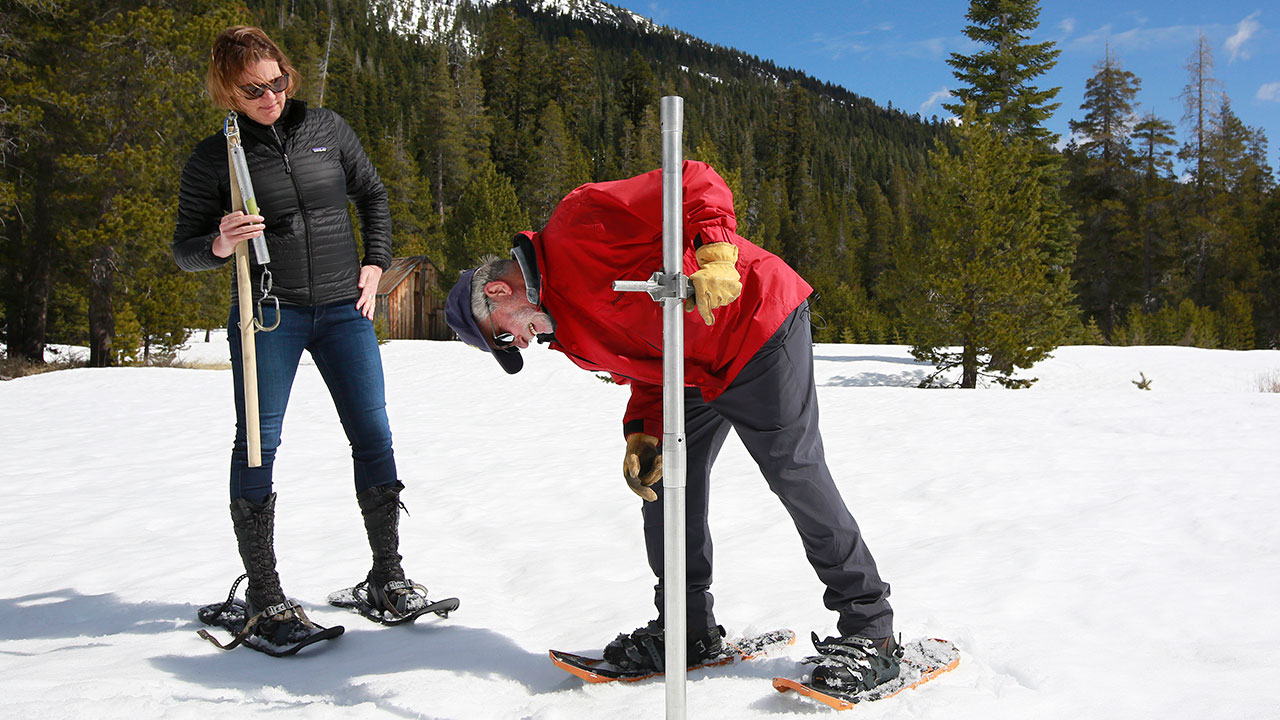 FILE - Frank Gehrke of the Department of Water Resources checks the depth of the snowpack during the snow survey, Monday, April 2, 2018, near Echo Summit, Calif.