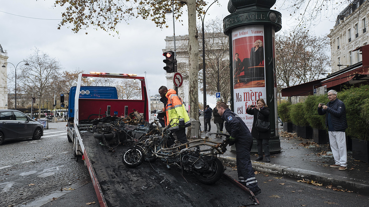 Workers clean up the street as they remove burned motorcycles, near the Arc de Triomphe, in Paris, Sunday, Dec. 2, 2018.
